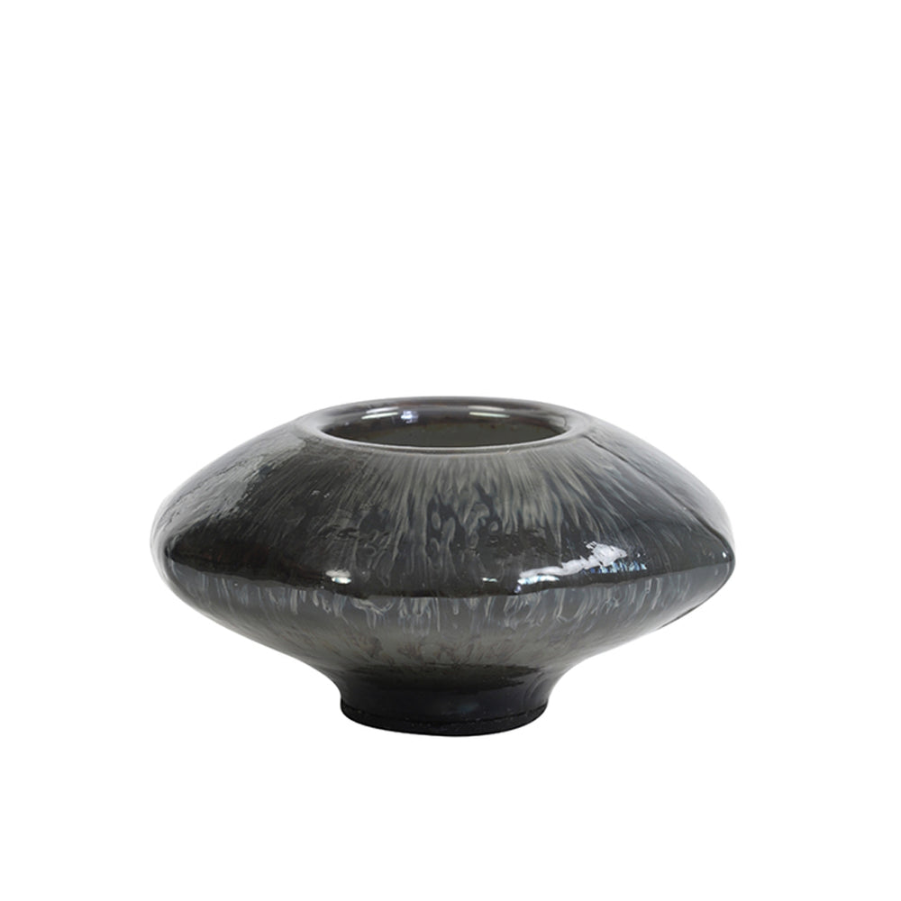 An iridescent blue/black/silver coloured tea light holder in a flying saucer shape, with a well at the top for a small candle to go.