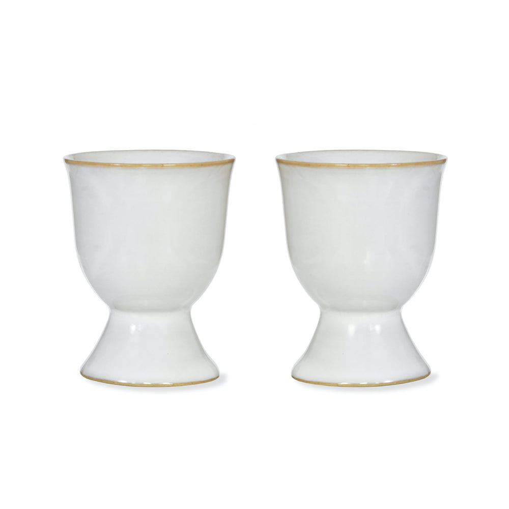 Two white ceramic egg cups with a straw coloured thin band around the top and base.