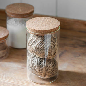 A cylindrical clear glass jar with a lid made from cork.