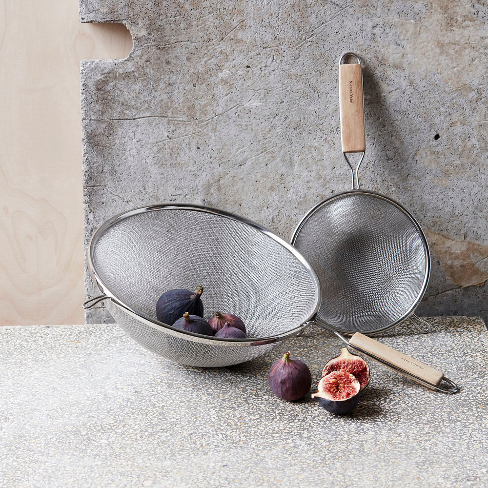 A set of 2 silver coloured metal sieves with light coloured wooden handles, one large and one small.