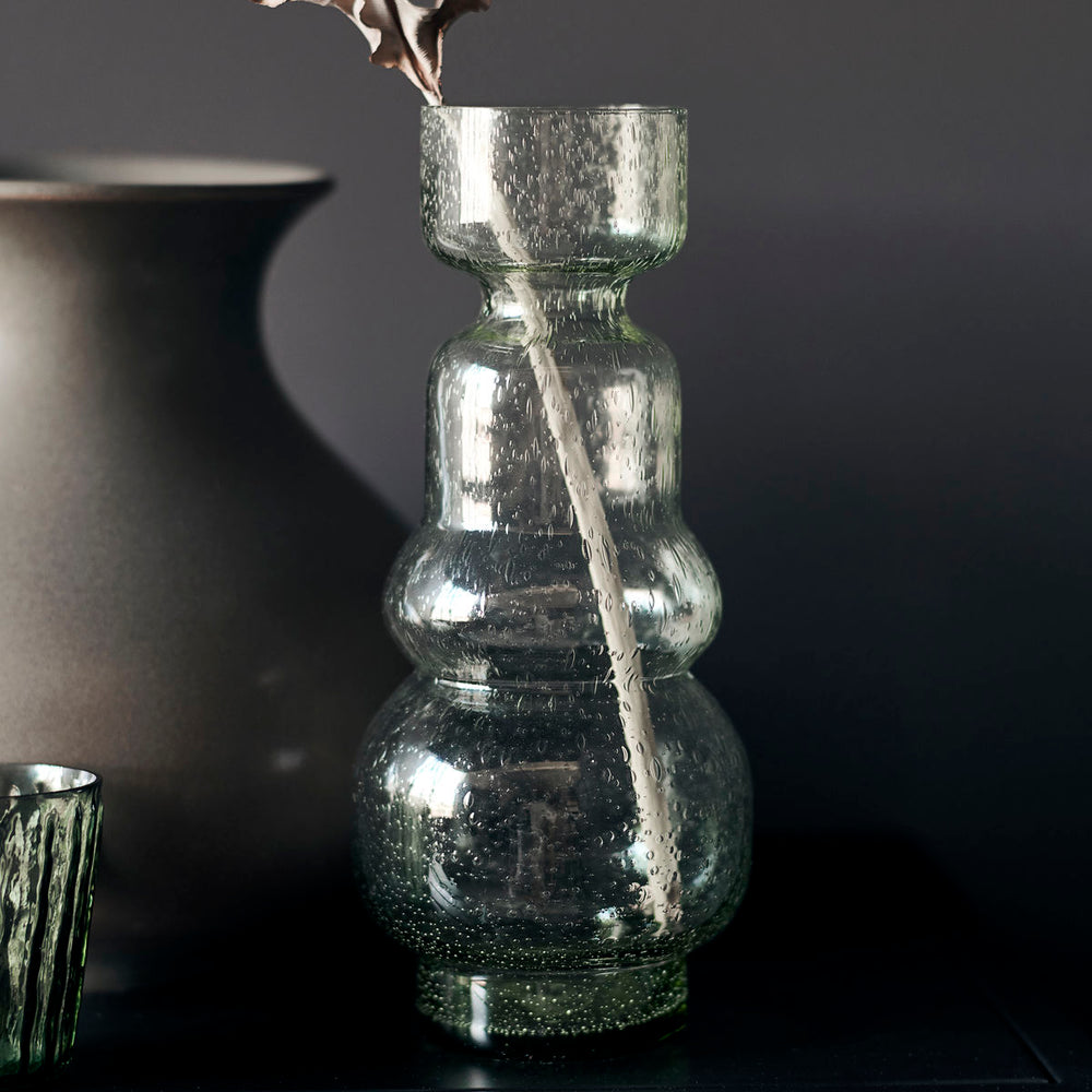 A light green glass vase in a sculptural banister-like shape, with small bubbles within the glass.