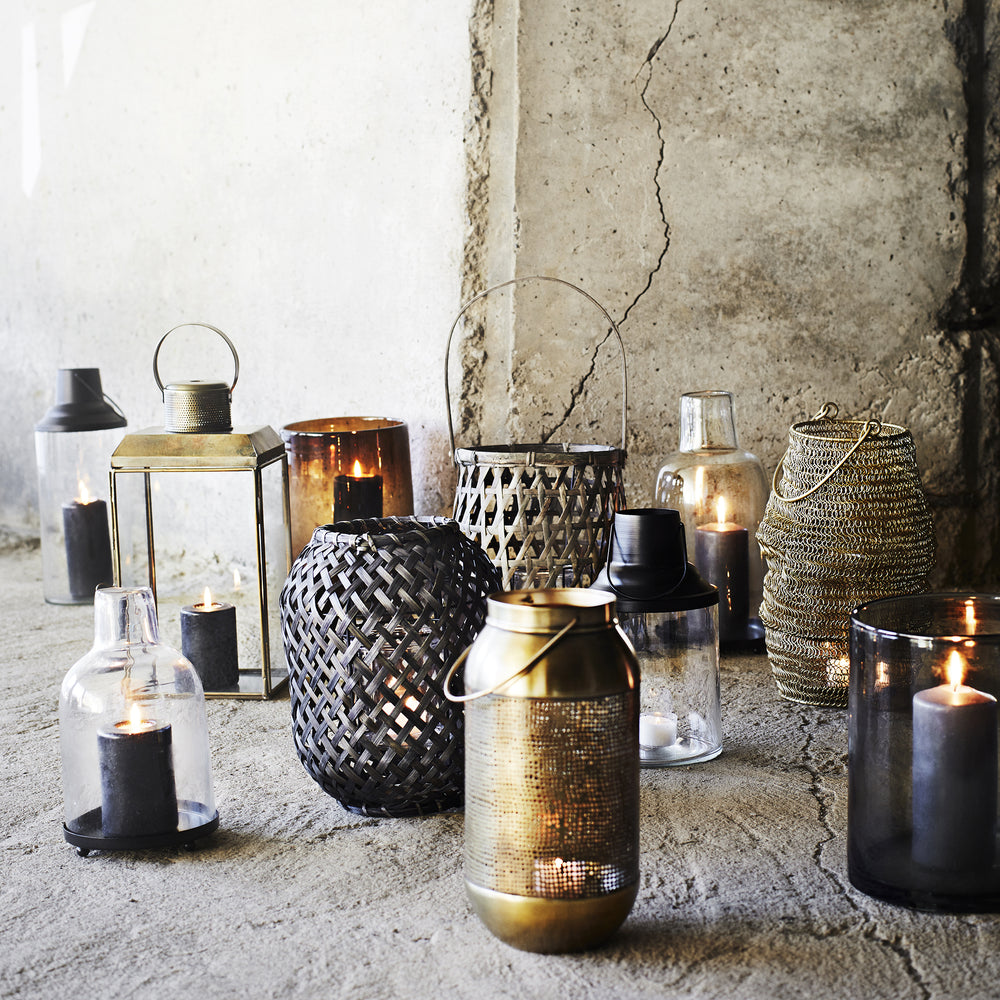 Load image into Gallery viewer, Glass lantern with bottle neck shape at top, sitting on a black iron circular base with lit black candle inside.