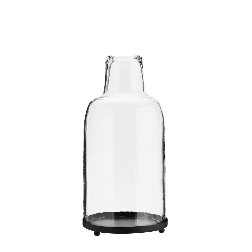 Glass lantern with bottle neck shape at top, sitting on a black iron circular base.