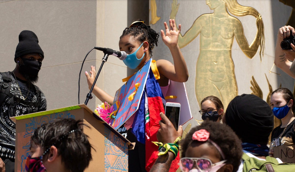 young girl wearing mask speaking at the podium of a Black Lives Matter protest in Brooklyn