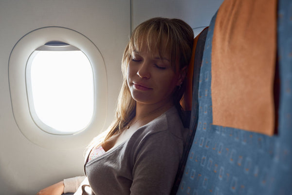 How to Sleep on a Plane, woman sleeping relaxed on plane