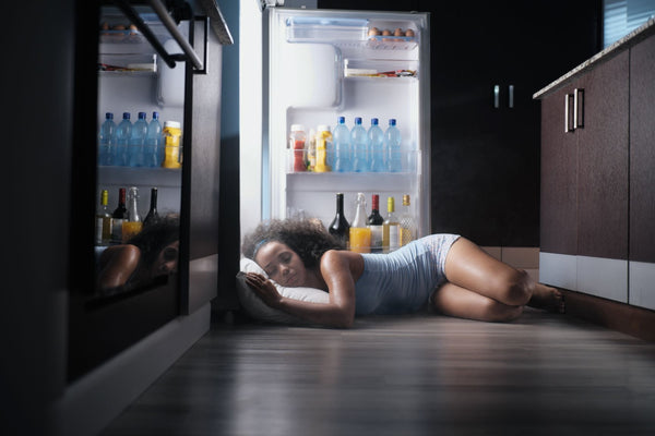 Best AC Temperature for Sleeping and Comfy Slumber Solutions, Woman sleeping in front of cold fridge