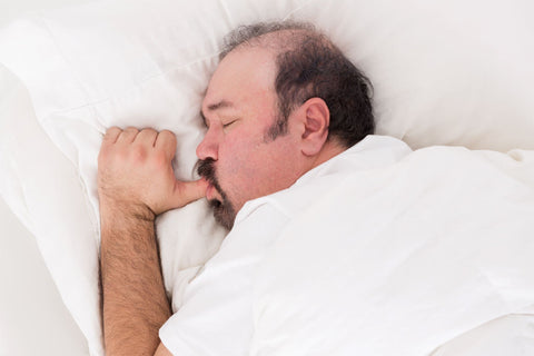 What Kind of Pillow Does a Stomach Sleeper Need? Man sleeping on stomach