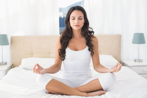 Practicing Yoga for better sleep, woman doing yoga in bed
