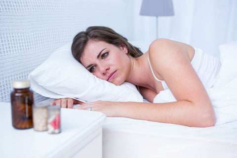 Don't overuse sleep medicines without medical advice, sleepless woman staring at pills on night stand
