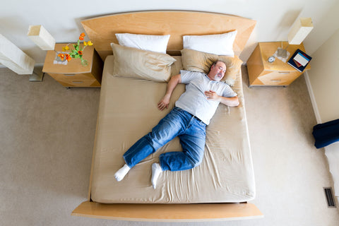 Combine two twin beds into a king, man enjoying lying on a king size bed