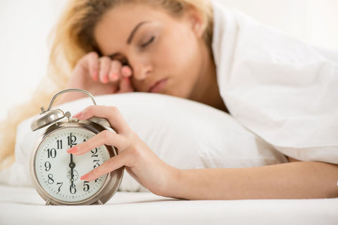 Avoid sleeping in and getting too much sleep, woman sleeping in and turning off alarm clock