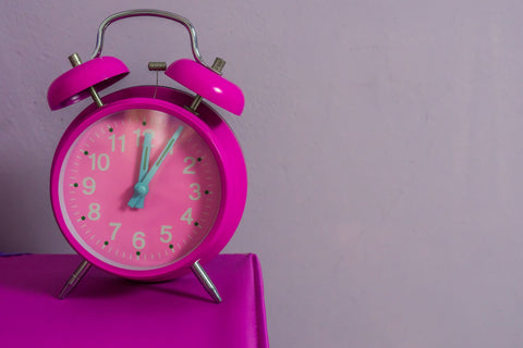 Is it okay to sleep 12 hours a day?, vintage pink alarm clock on bedside table