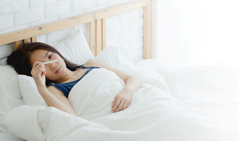 Sleeping with high fever, woman in bed looking at thermometer