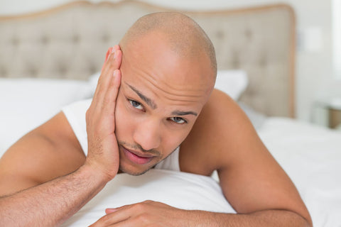 How To Fall Asleep With a Toothache, man holding his teeth with pain in bed