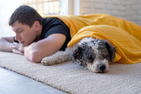 young man sleeping with his dog comfortably on the floor