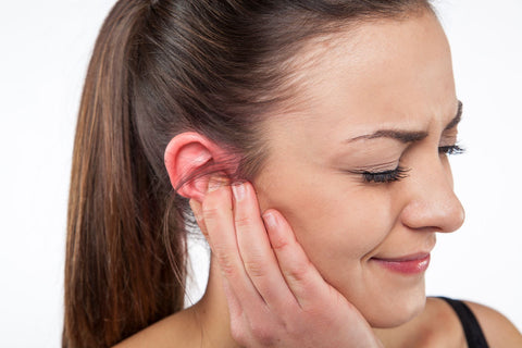 Ear infections and impact on sleep, woman holding her ear in pain