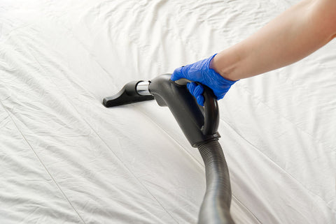 vacuum a mattress to dry it, mattress being vacuumed by hand