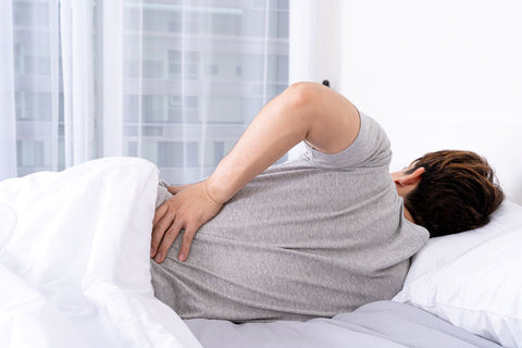 Contour pillows help with spinal alignment and avoid back pain after sleep, man holding his back when waking up