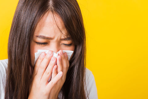 Ways to deal with a stuffy nose and sinus infection, woman blowing her nose