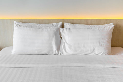 Changing your pillow for a good night's sleep, bed with several pillows arranged on top