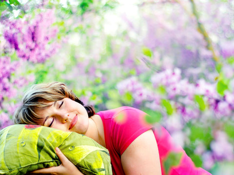Natural desinfecting of pillow via sunlight, woman outside on pillow with lavender in background