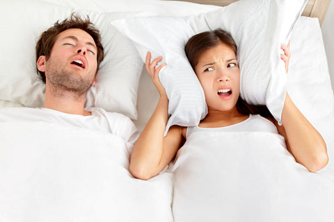 What are the other symptoms of sleep apnea, couple in bed with snoring man and woman covering her ears
