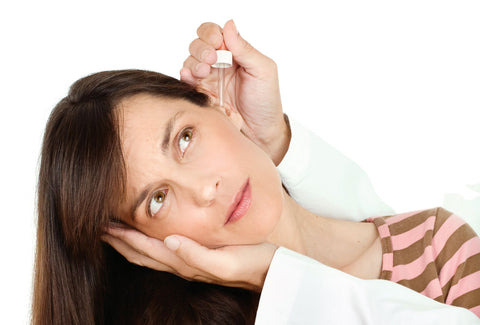 Remedies for ear infections, woman getting ear medication