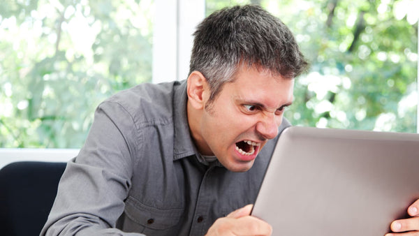 man screaming at laptop, angry man at desk because he's tired, what happens when you don't sleep from snoring, decreased productivity from snoring man at desk angry