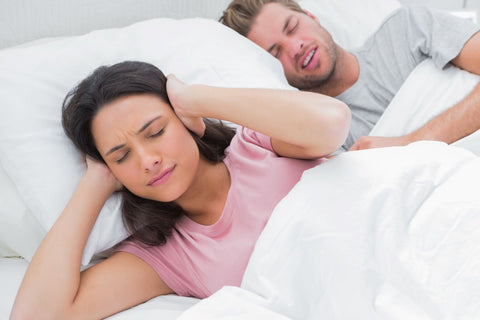 How to block out snoring sounds, woman in bed due to snoring partner