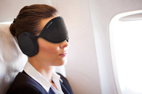 business woman on air plane using Hibermate sleep mask with ear muffs