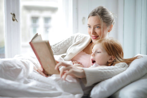 Woman reading to tired daugher child in bed