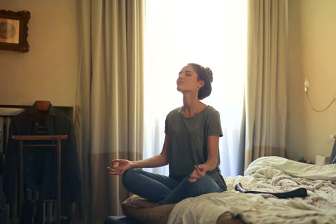 Relax before bed for more dreams, woman sitting on bed meditating