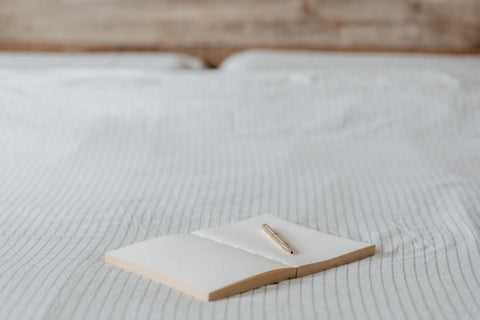Dream journaling, journal and pen lying on bed