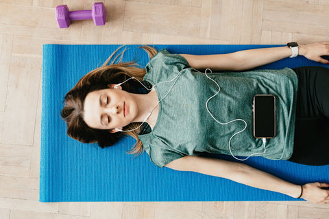 Reduce stress levesl with exercise to stop mouth breathig during sleep, woman on exercise mat relaxing