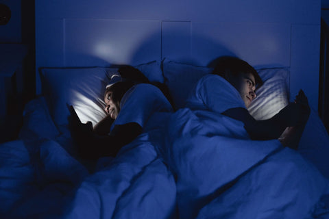 Reduce screen time before bed to improve quality of sleep, couple in bed using smartphones