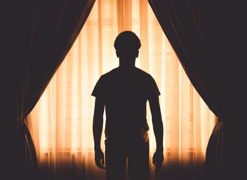 keep your bedroom dark and cool when sleeping with a stuffy nose, man in front of a window curtains