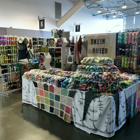 Skein Queen Stand at Southern Wool Show 2020 with lots of skeins of yarn in a rainbow of colours