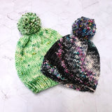 Photo of two bobble hats, one is bright green and one is black with a white section where bright coloured speckles can be seen