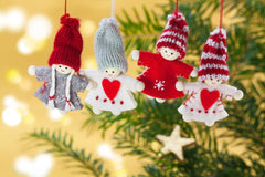 Picture of 4 knitted christmas characters hanging from a christmas tree