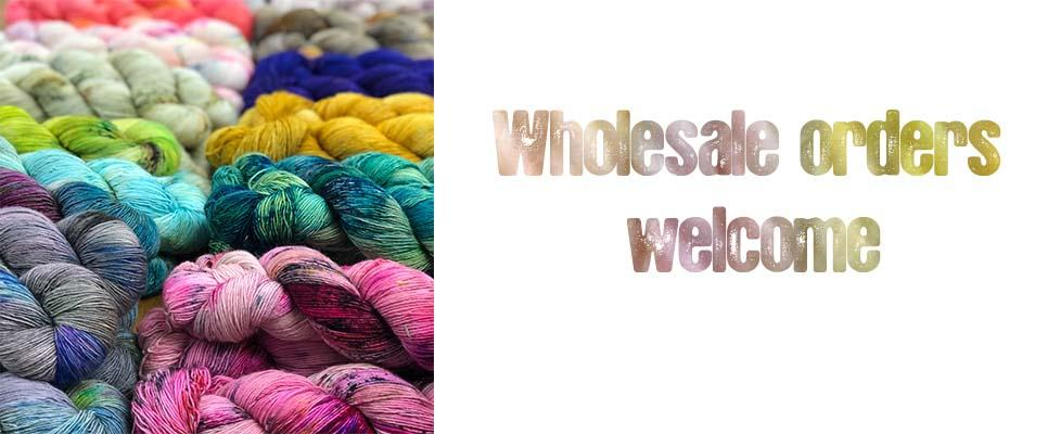 Photo of table covered in skeins of yarn with text wholesale orders welcome
