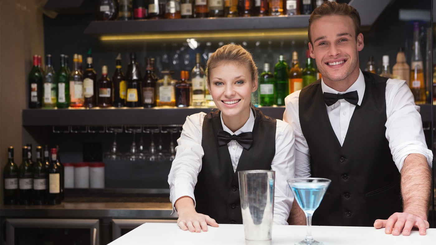 Man and woman bartenders smiling in bow ties