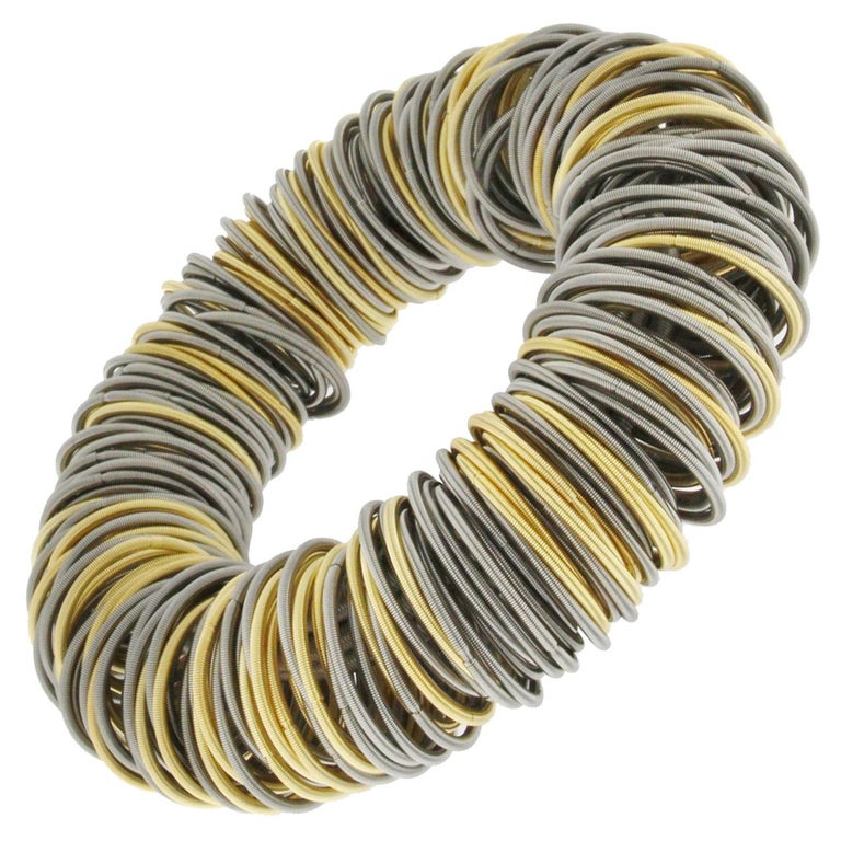 Balanced between the exotic and the industrial the Maxi One stainless steel and gold plated bracelet is strikingly elegant. The hardness of steel is softened by a clever structure of elastic hoops of finely spun springs some plated with gold. By