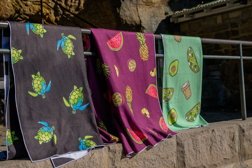 Three Lazy Wombat sand free beach towels hanging at the beach, turtles, fruit and avocado