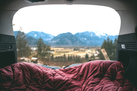 View out of the back of a hatchback showing mountains in the distance.
