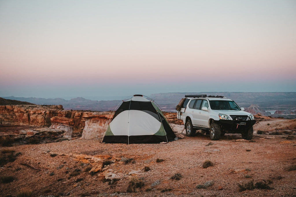 A tent and a camper truck atop a canyon at sunset.