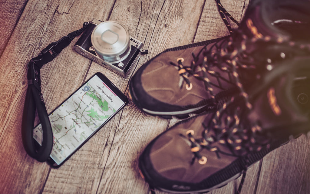 A pair of hiking boots, a vintage camera, and a smartphone showing Google Maps on a rustic wooden background.
