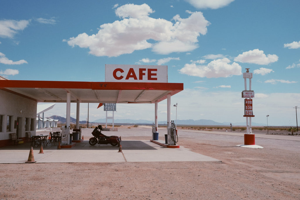 Motorcycle parked at a gas station in the middle of a sunny desert.