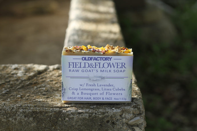 the healthy promise soap handcrafted goats milk field and flower front on stone wall
