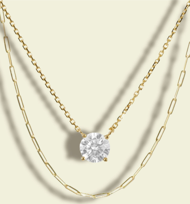 a round cut moissanite solitaire necklace on a gold chain and a gold long loop chain necklace by gypphy ethical jewelry