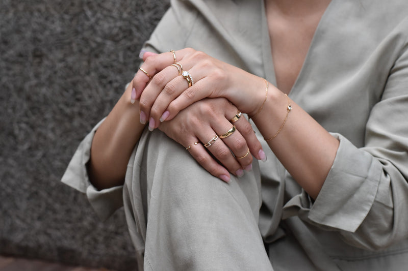 a woman in a grey silk shirt and pants sits with her hands folded on her knee. On her hands are ethically sourced moissanite rings
